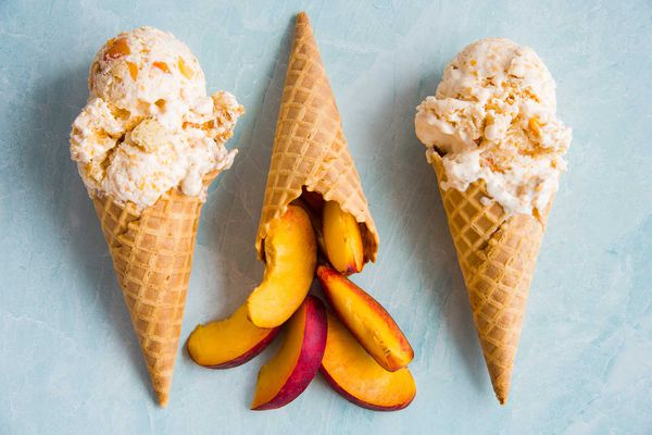 Two homemade peach cobbler ice cream cones are set on either side of a cone with sliced peaches.