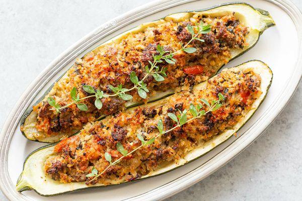 Italian zucchini recipe of two sausage stuffed zucchini on a platter.