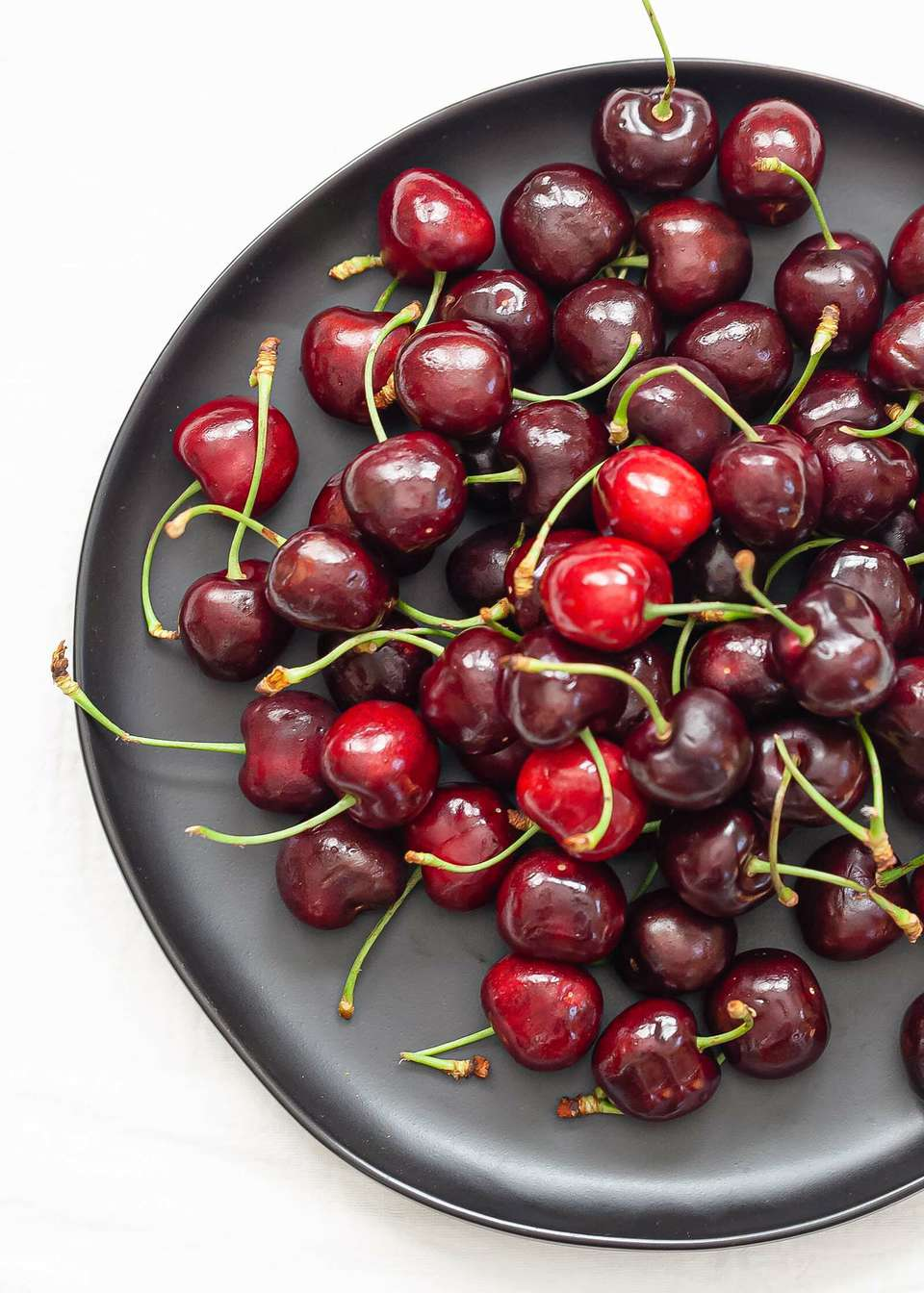 Overhead view of a dark plate with bing cherries piled in the center to show how to choose the best cherries.