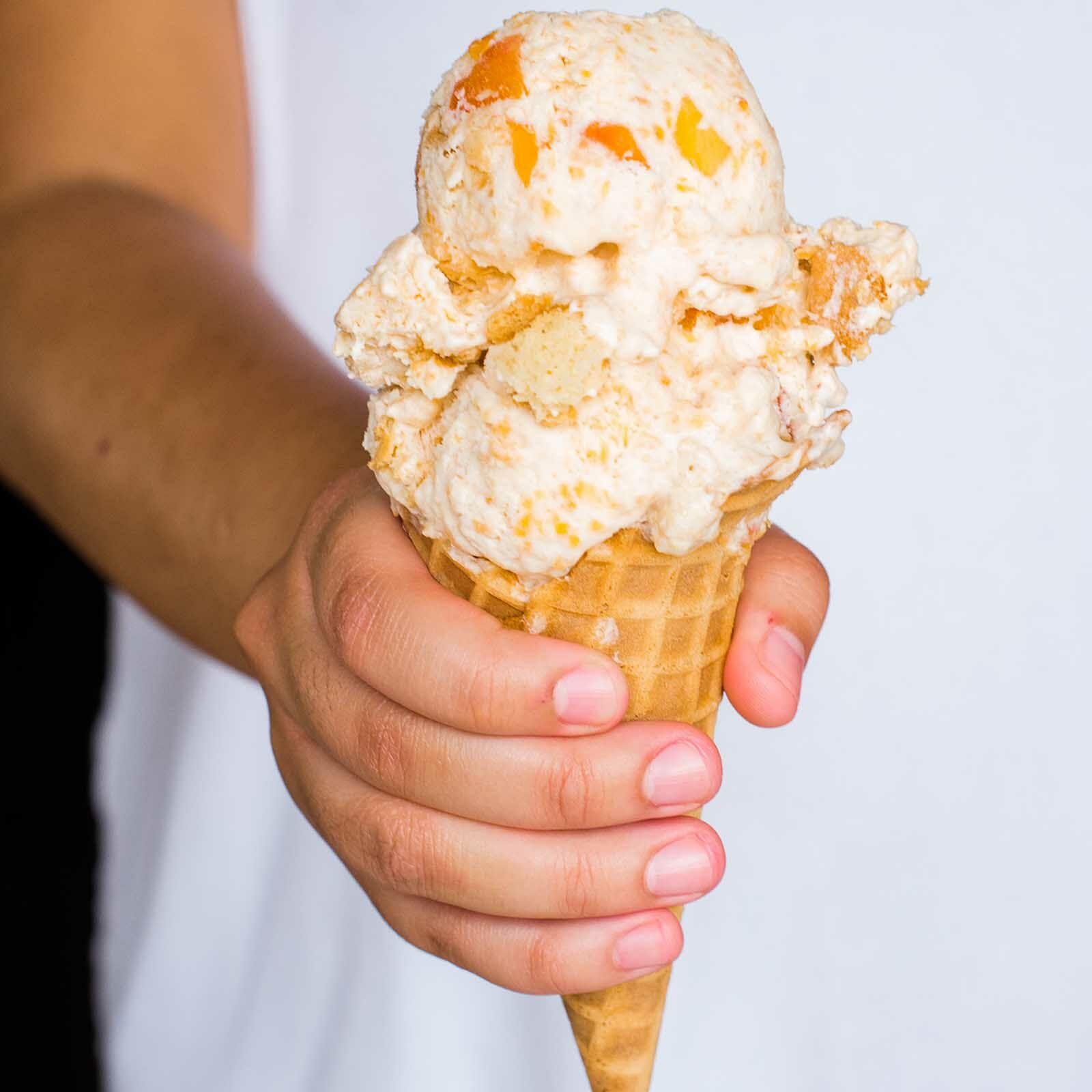 A hand holds a peach cobbler ice cream cone.