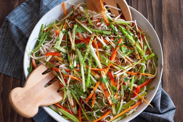 Overhead view of an easy rice noodle salad in a serving bowl along with wooden claws.