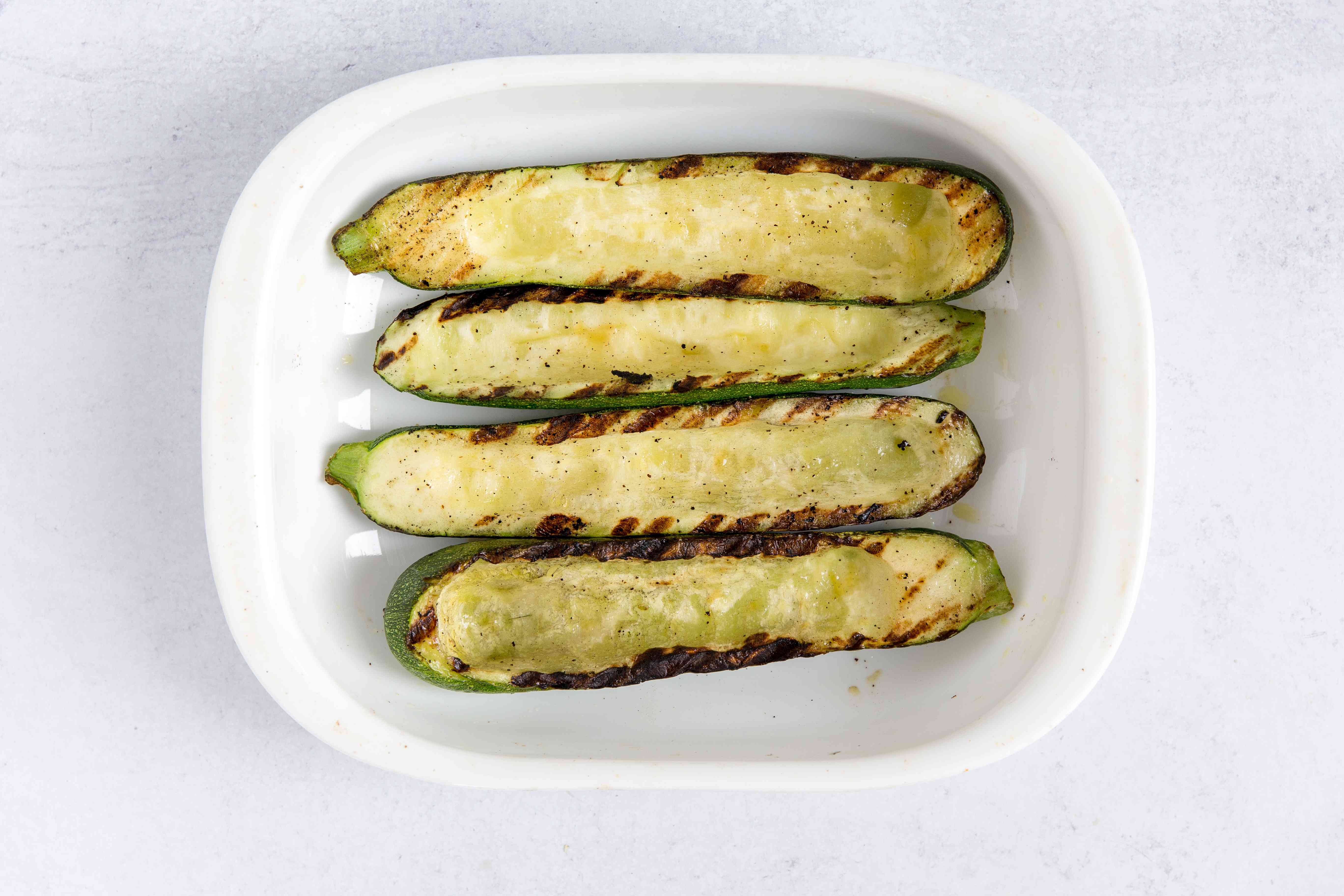 Grilled zucchini in a baking dish.