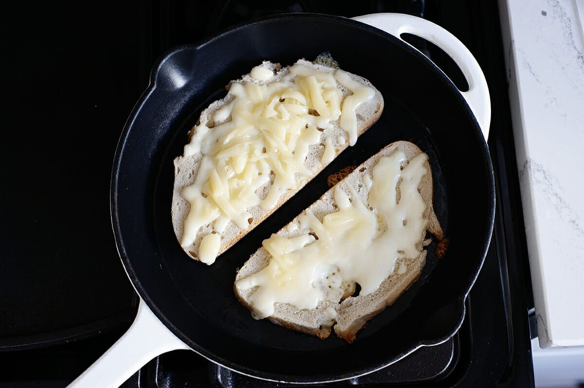 Two slices of bread, set open faced with shredded cheese on top in a cast iron skillet.