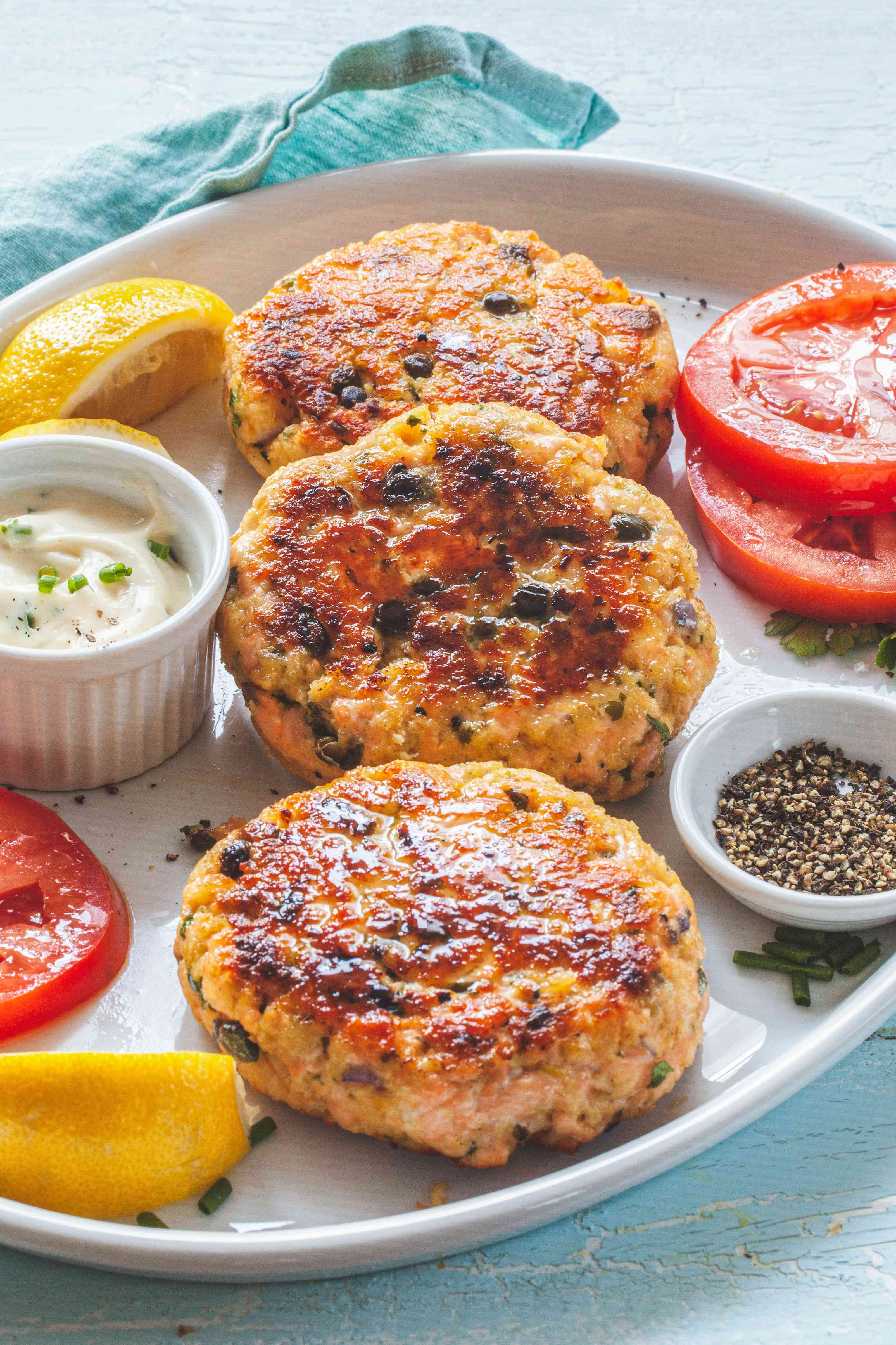 Perfect salmon burger patties on a platter with lemon, tomato, and sauce.
