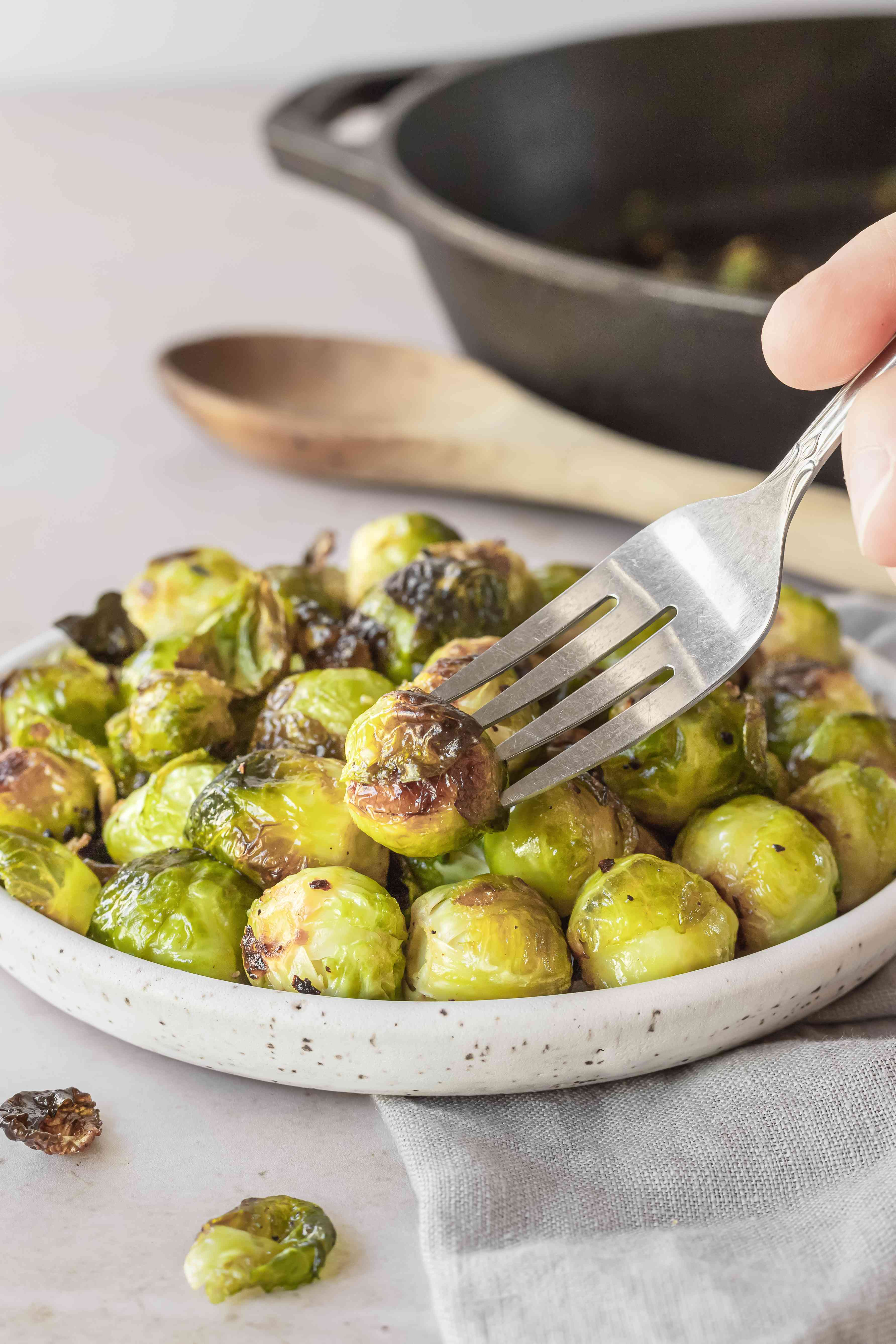 A fork picking up a roasted brussel sprout.
