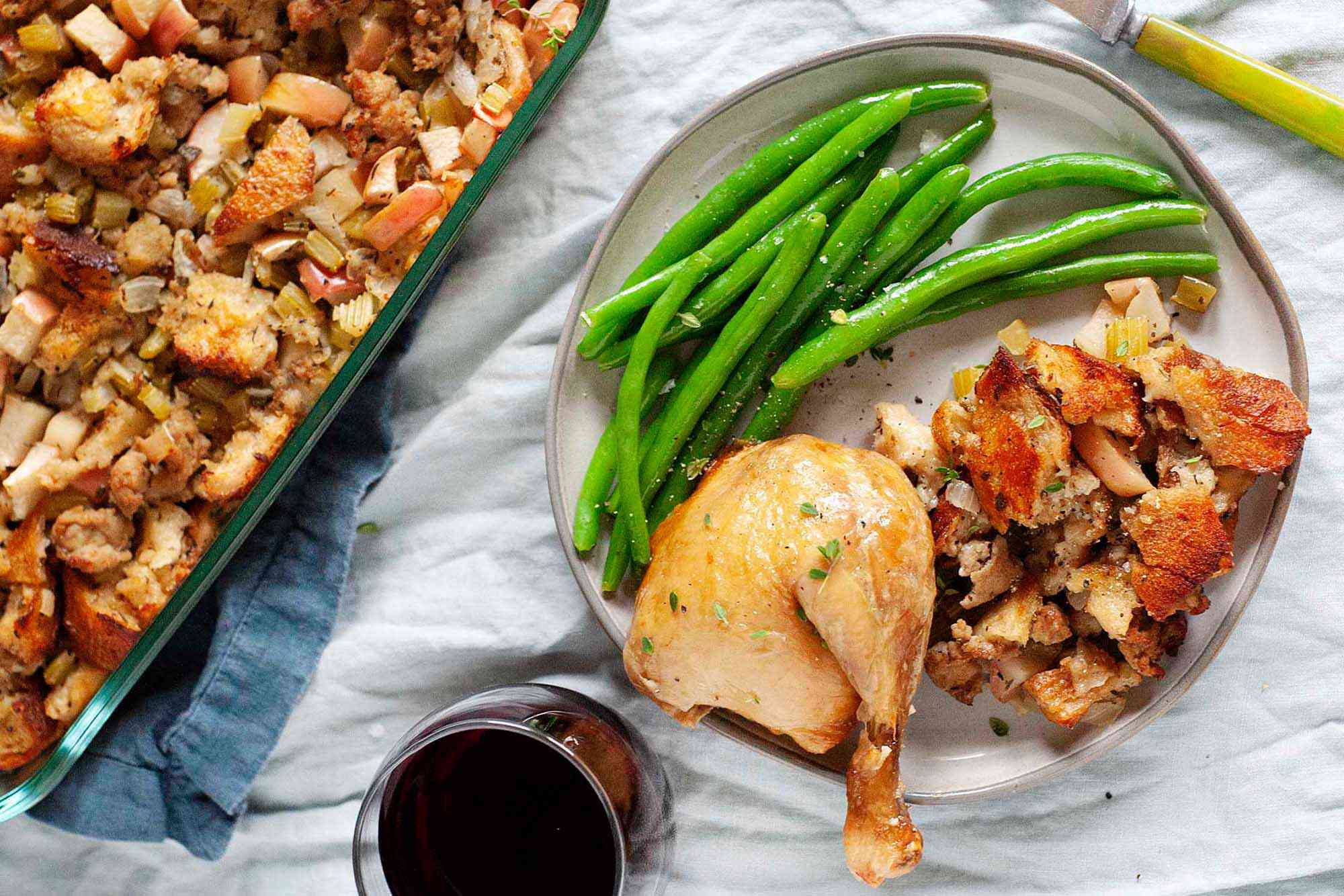 A baking dish with classic sage, sausage and apple stuffing next to plate of stuffing, chicken leg, and green beans. There is a glass of red wine nearby.