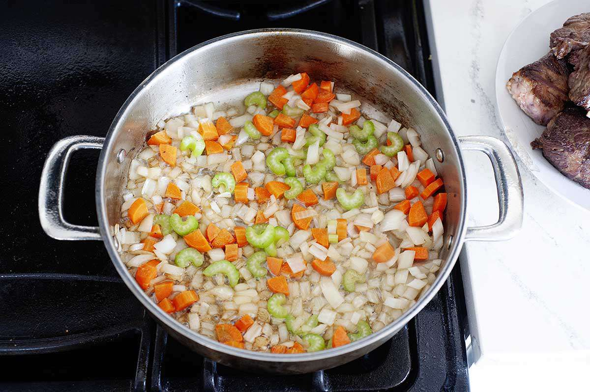Vegetables sautéing in a pan for a beef short ribs recipe.
