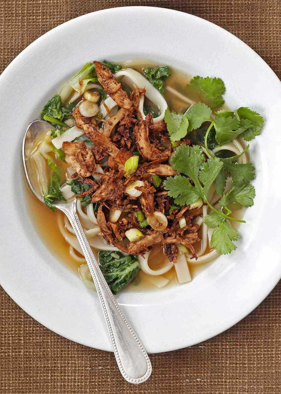 Gochujang Chicken and Udon Noodle Soup in a white bowl with a spoon and fresh herbs.