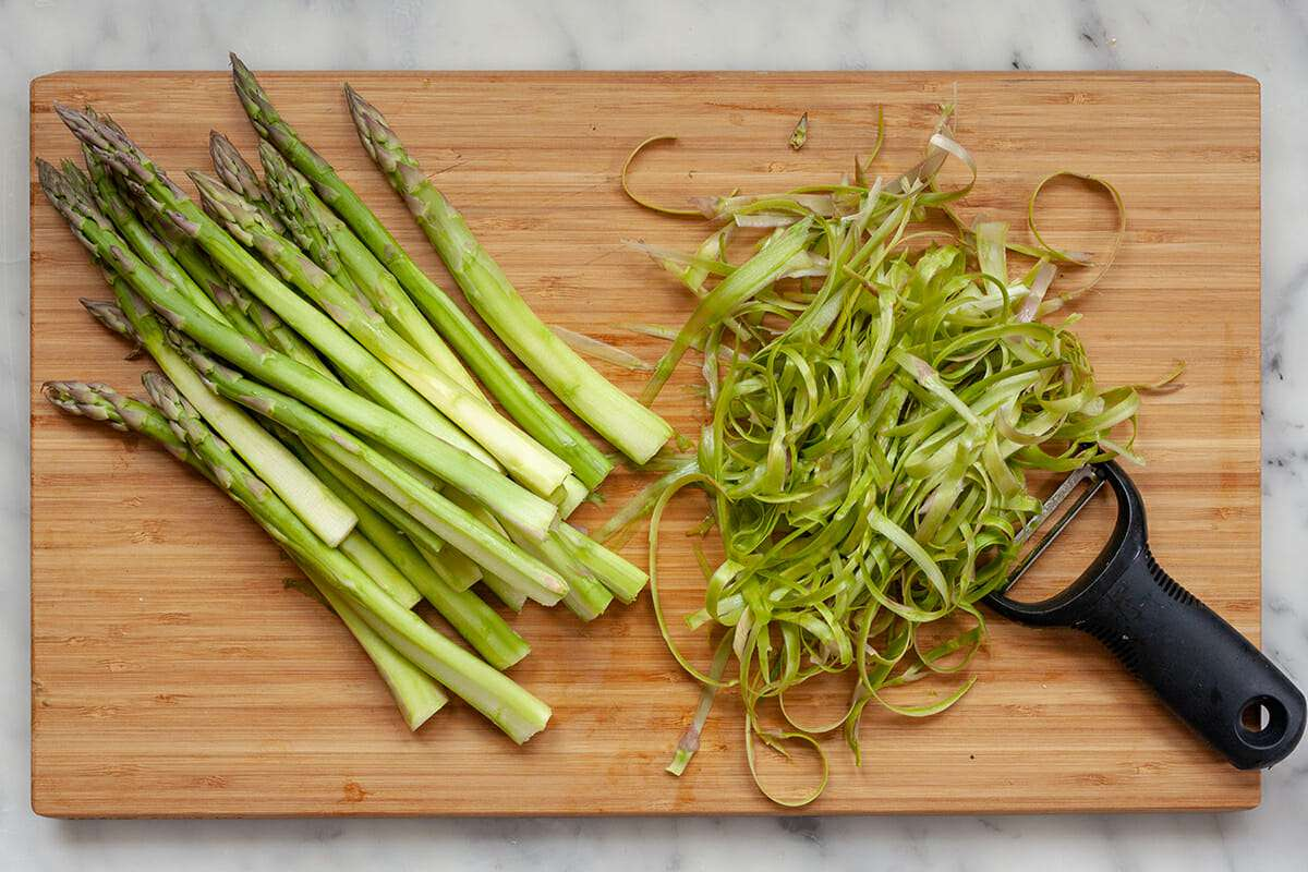 Bruschetta with Asparagus - peeled asparagus on cutting board with peelings nearby