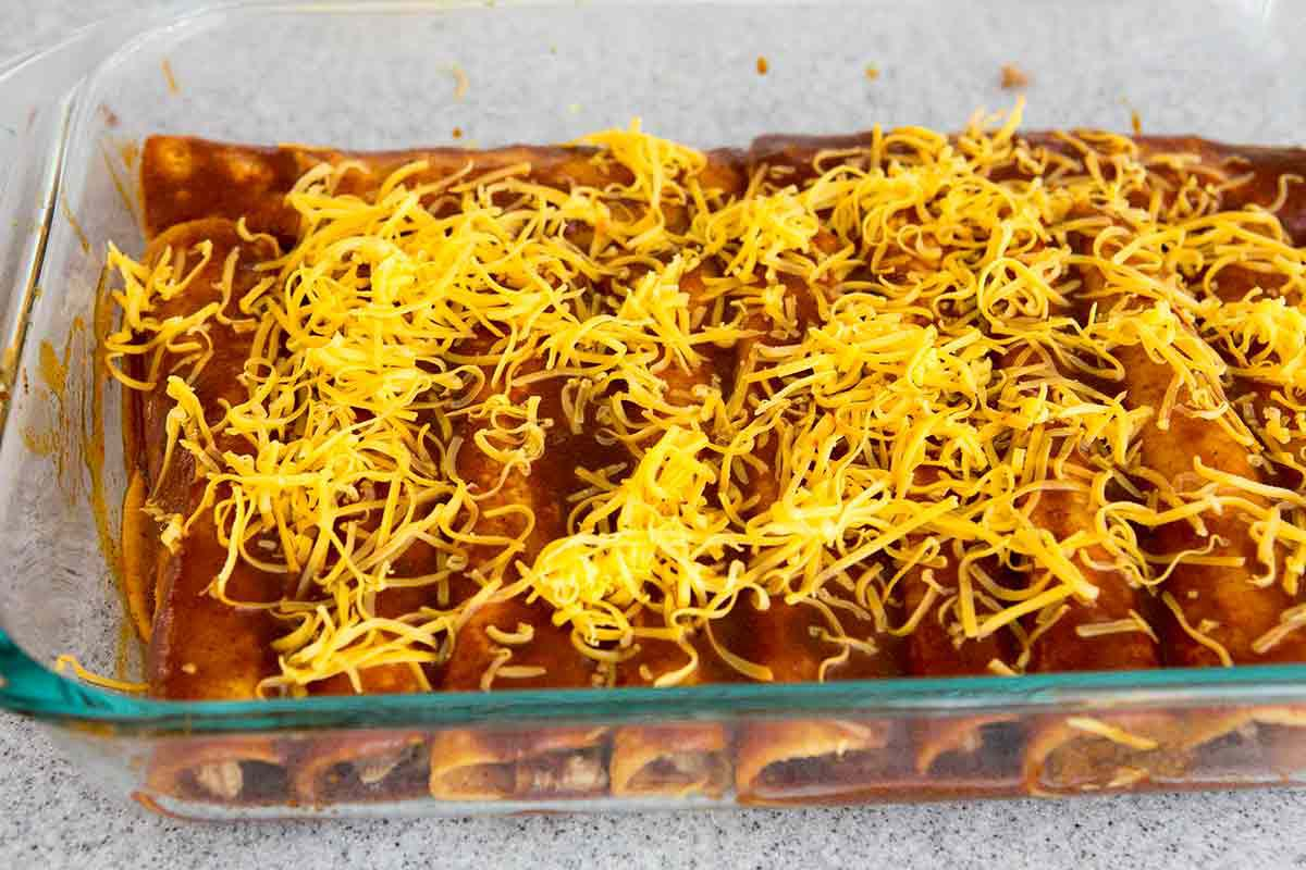 sprinkle homemade chicken enchiladas with grated cheese