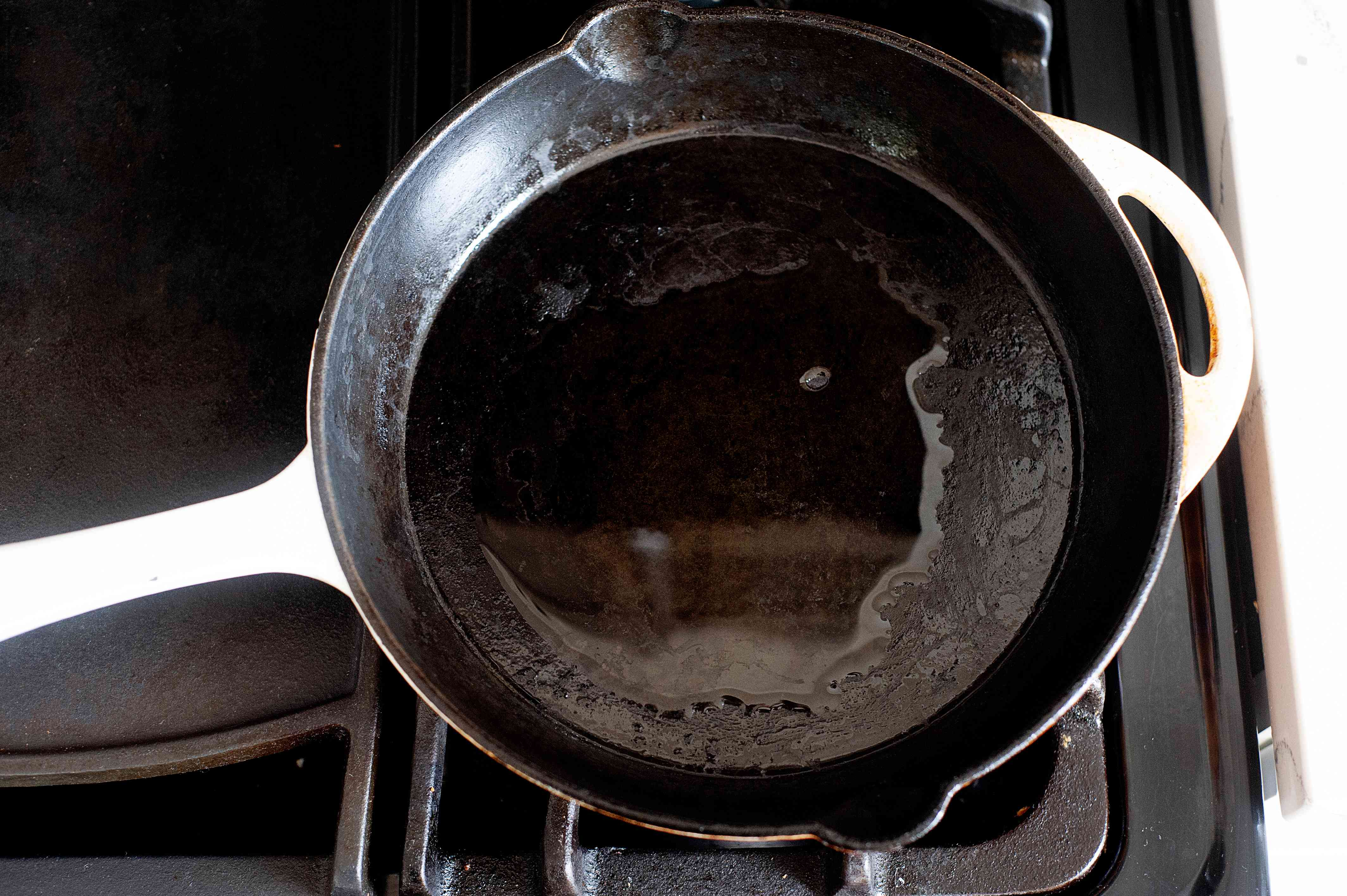 Skillet on the stove with oil in it to make a Socca Flatbread Recipe.