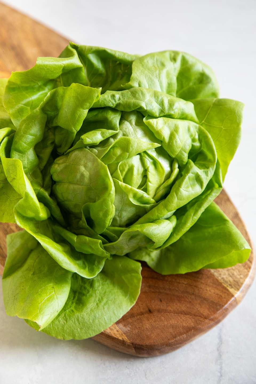 Head of lettuce on a wood cutting board
