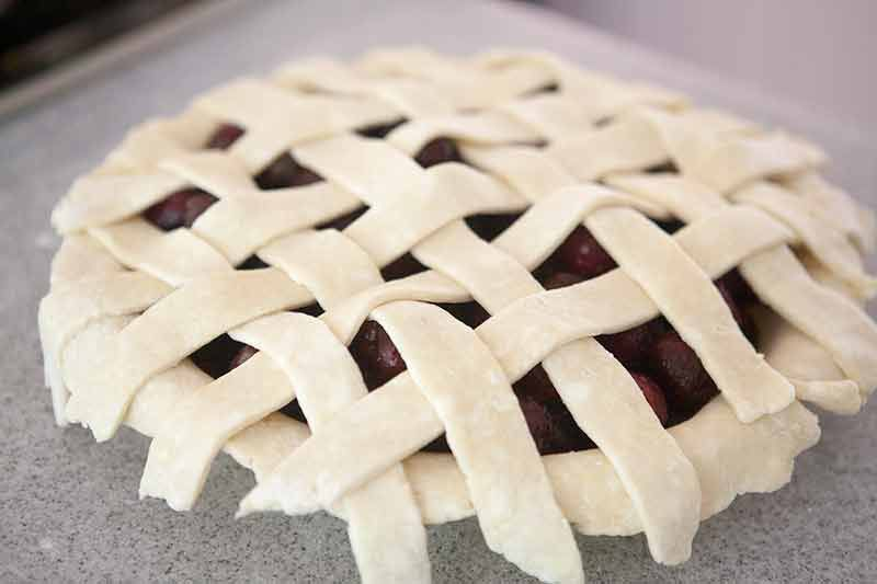 Unbaked homemade cherry pie on a counter and filled with cherry pie filling. A lattice top crust is constructed over the sweet cherries.