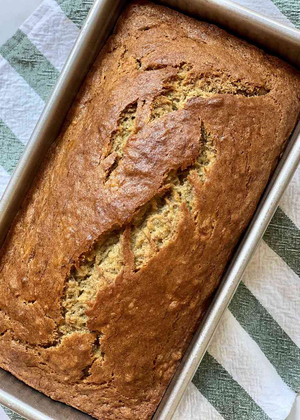 The best gluten free banana bread in a pan with a linen towel underneath.
