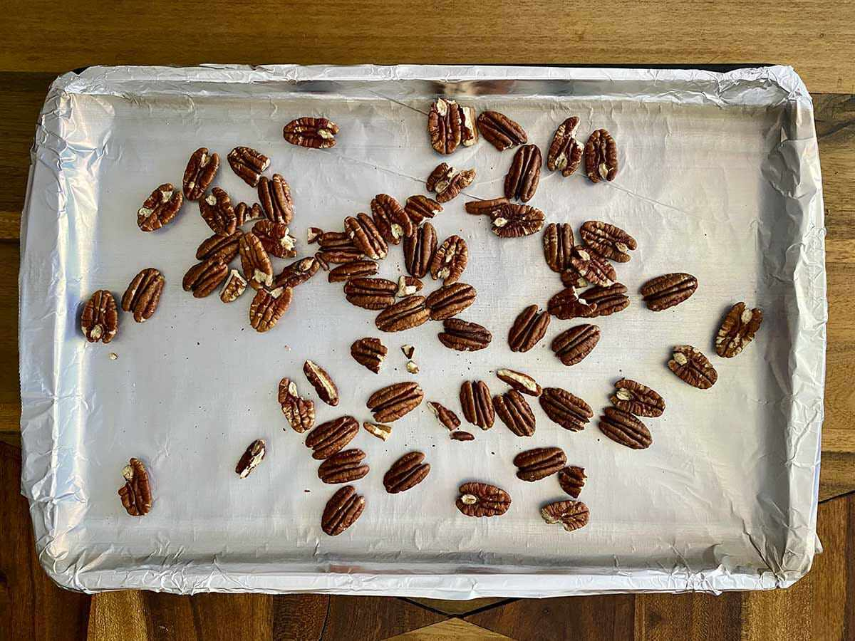 A foil covered baking sheet with whole pecans spread on it to make a Fall Vegetable Salad with Bacon and Maple Dijon Vinaigrette.