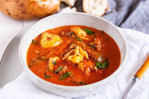 One-Pot Tortellini Soup - white bowl with tomato soup, fresh basil and cheese filled tortellini