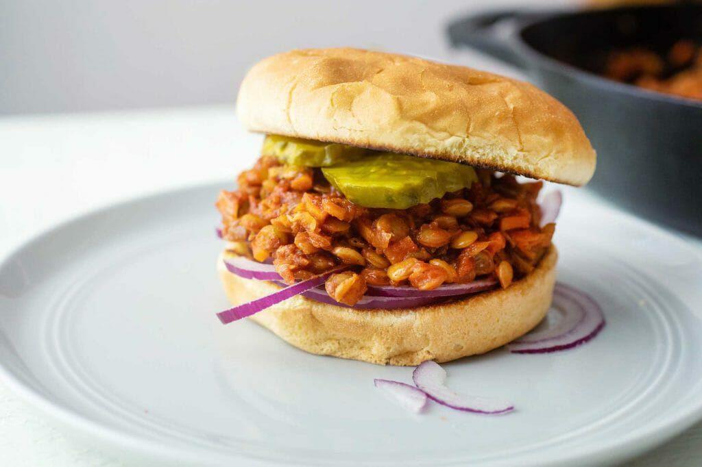 Vegan lentil sloppy joe burger with onions and pickles