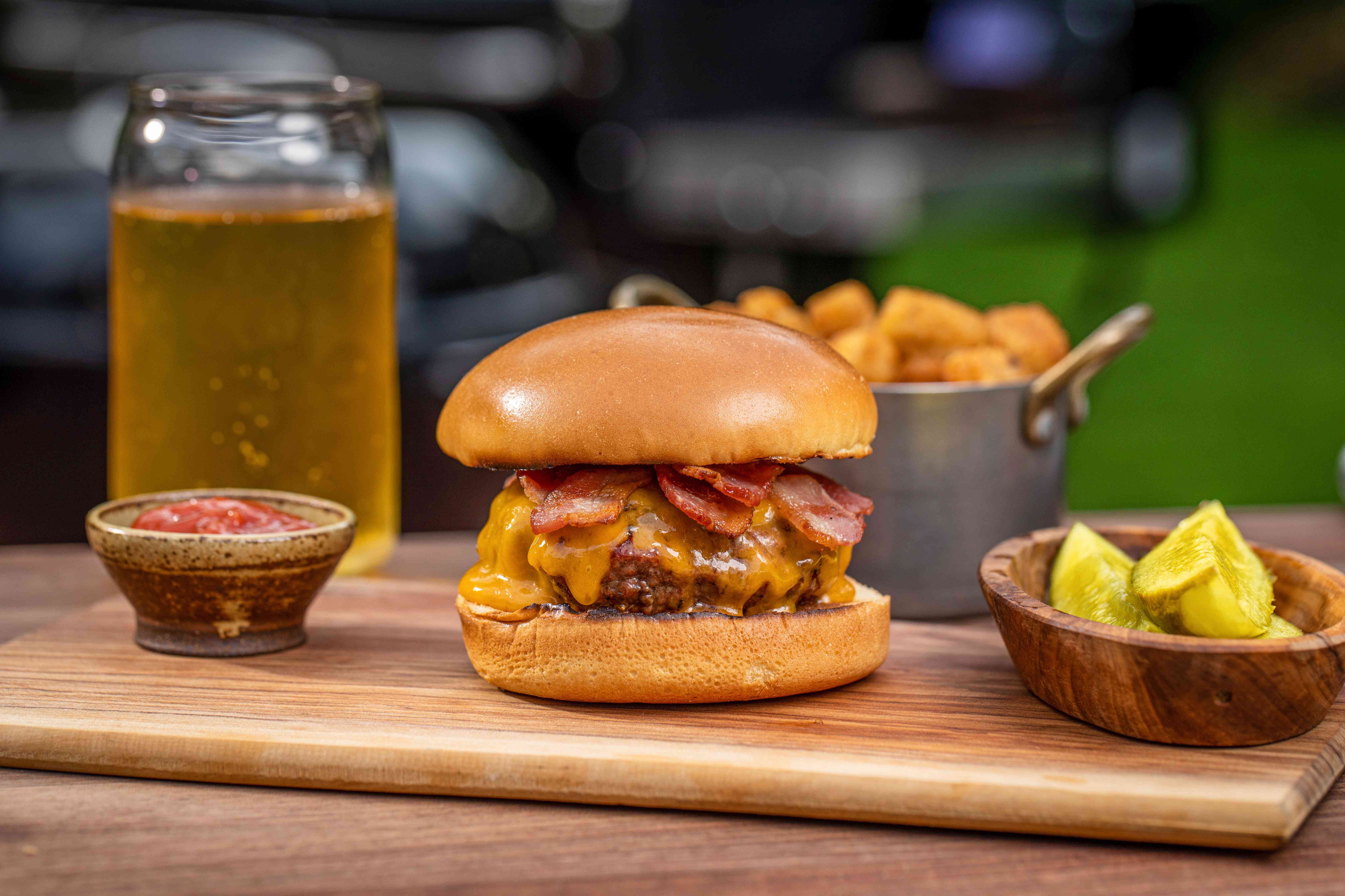 Side view of a perfect bacon cheeseburger outside on a wood cutting board with pickles, beer, and spices set around it.