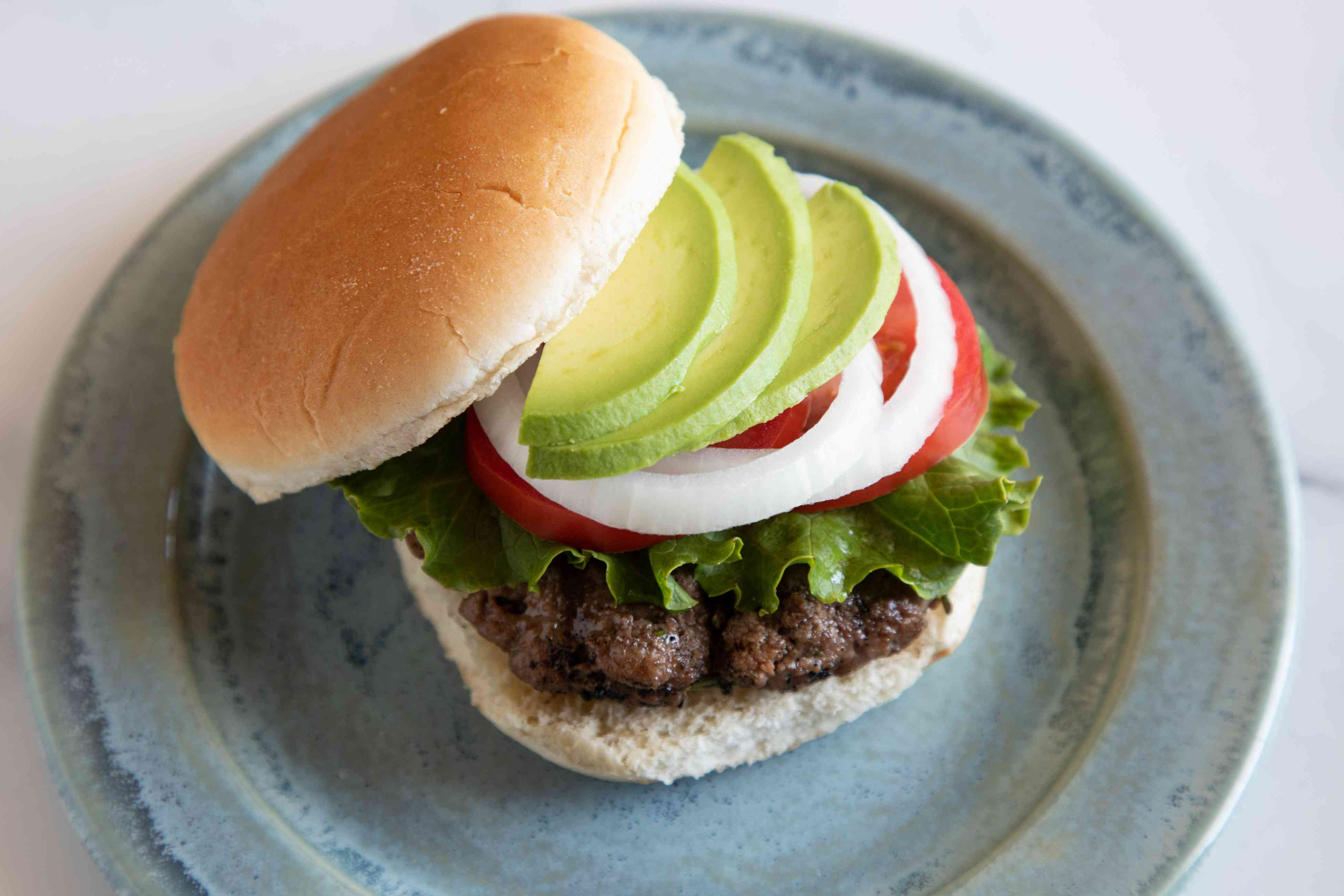 A famous burger topped with avocado on a plate.