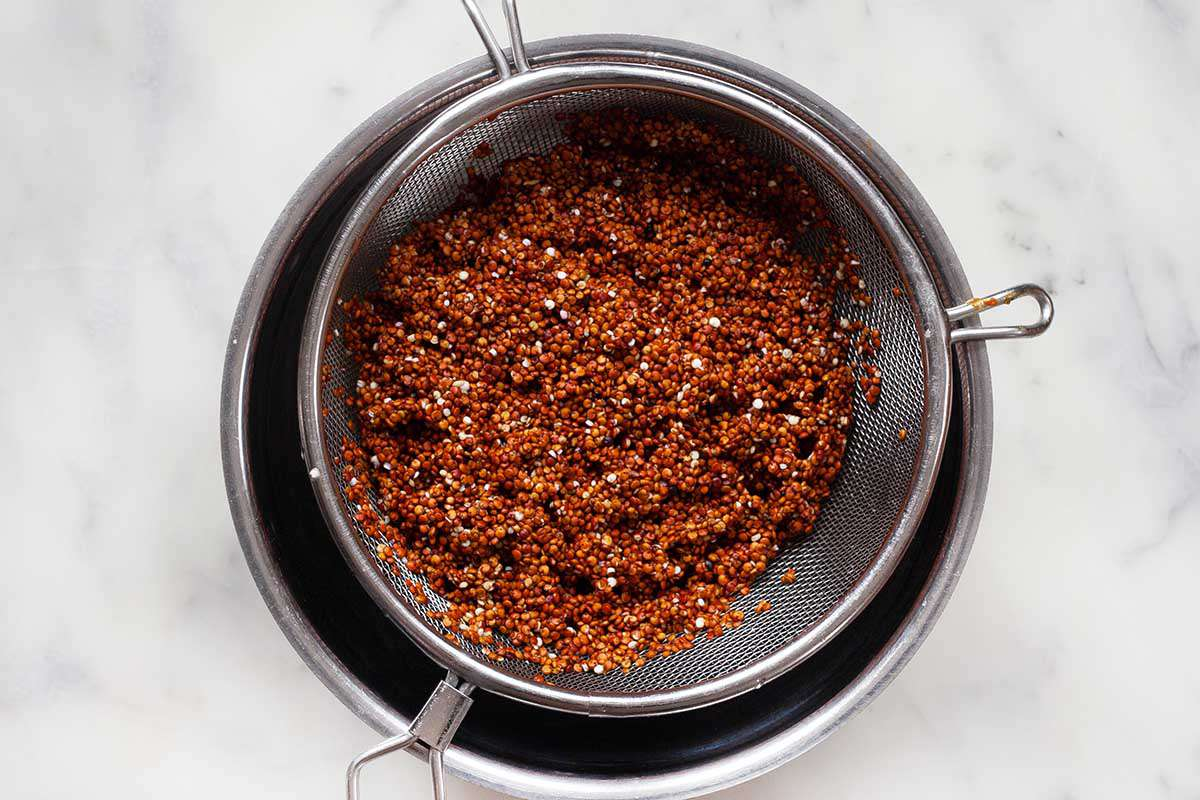 Red quinoa in a colander sitting over a metal bowl on a marble background.