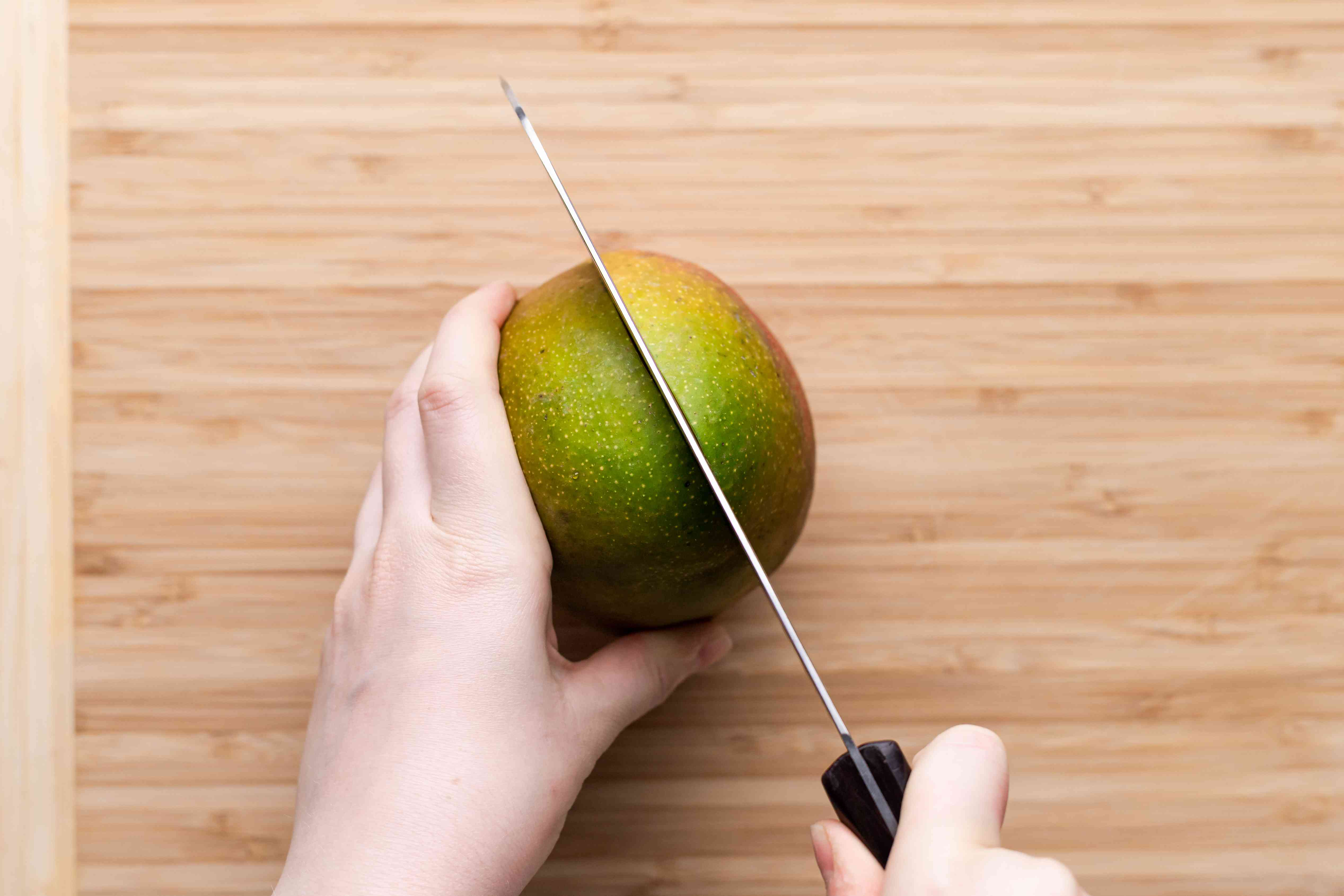 A person holding a knife and cutting into a mango to show how to cut a mango.