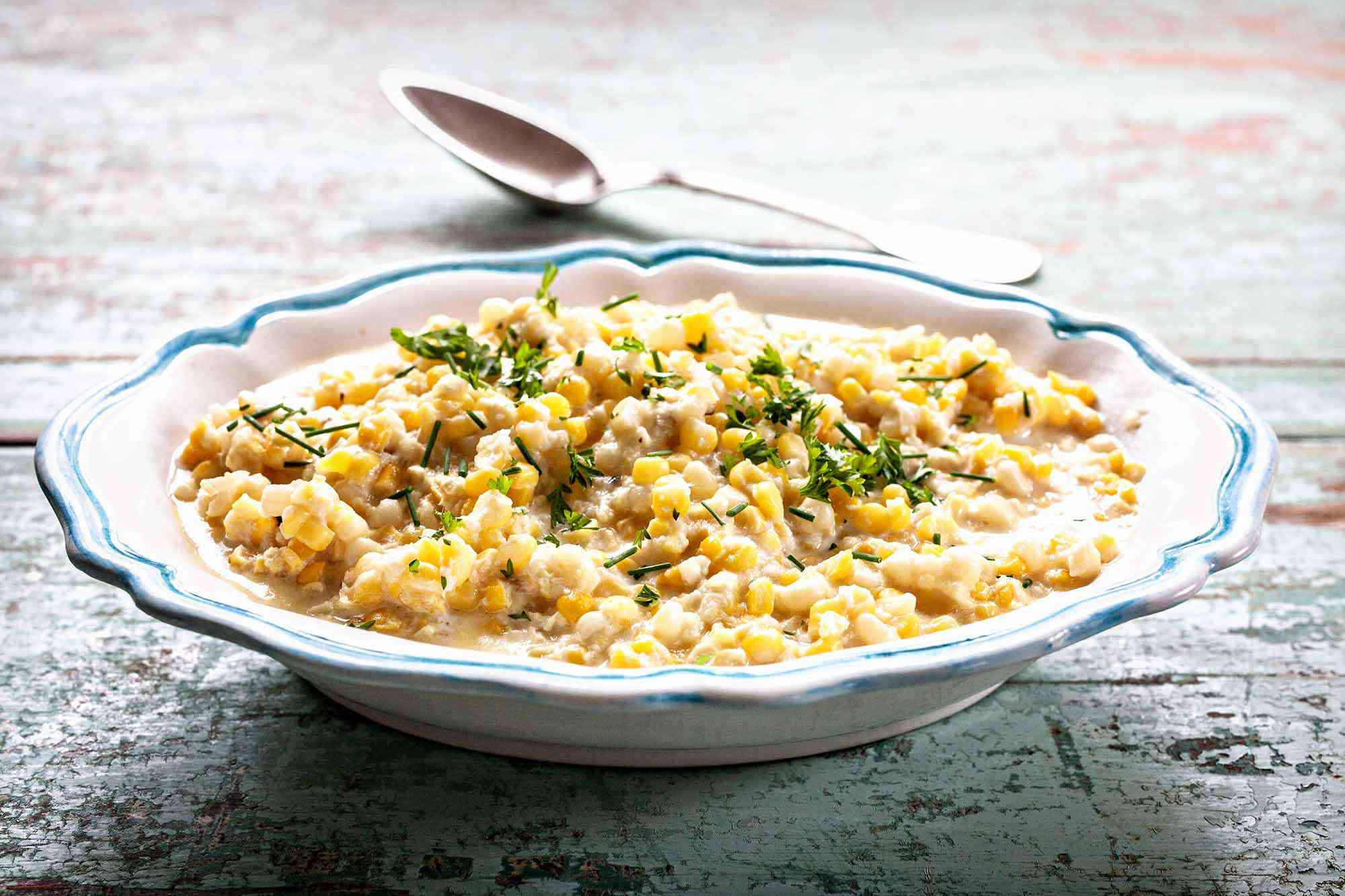 Best Creamed Corn Recipe - bowl of creamed corn wtih spoon and herbs