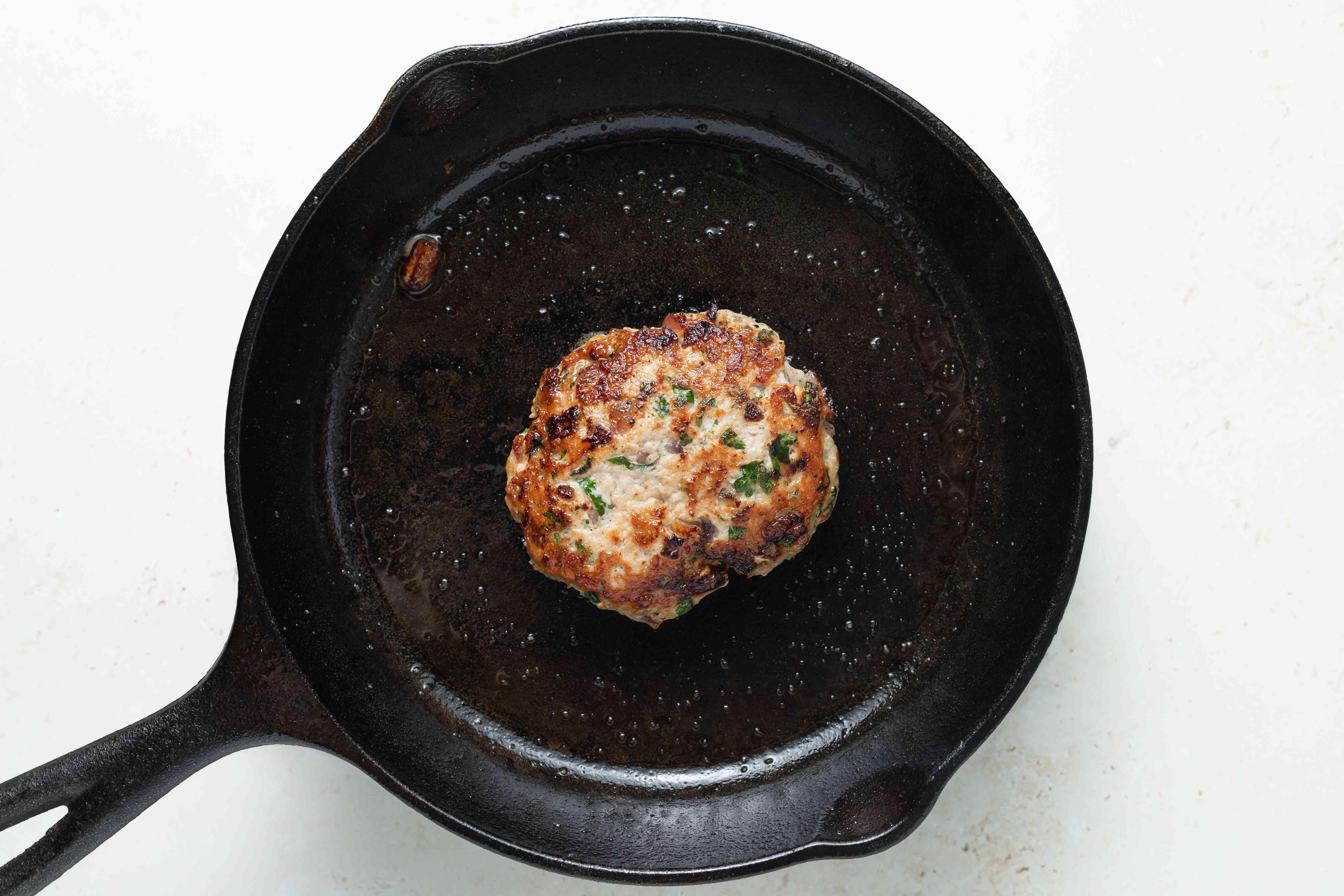A cast iron skillet pan frying a turkey burger for a best turkey burger recipe.