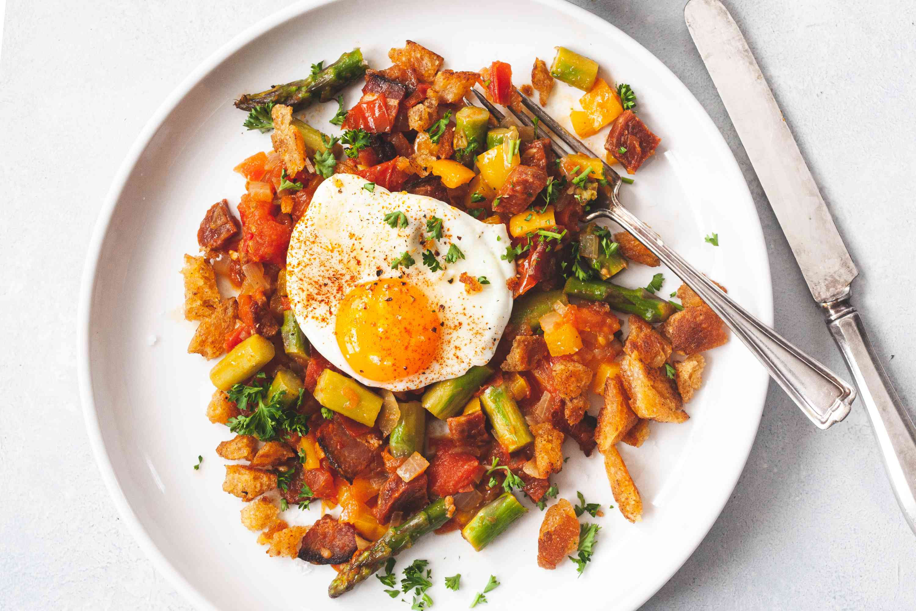 Overhead view of a white plate with Spanish Style Migas with Asparagus, Chorizo, Bacon, and Eggs.