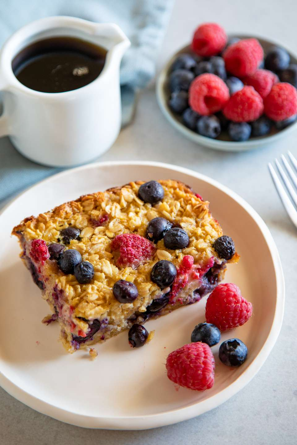 Baked Oatmeal Bars served on a plate and topped with berries with maple syrup and extra berries set behind the plate.