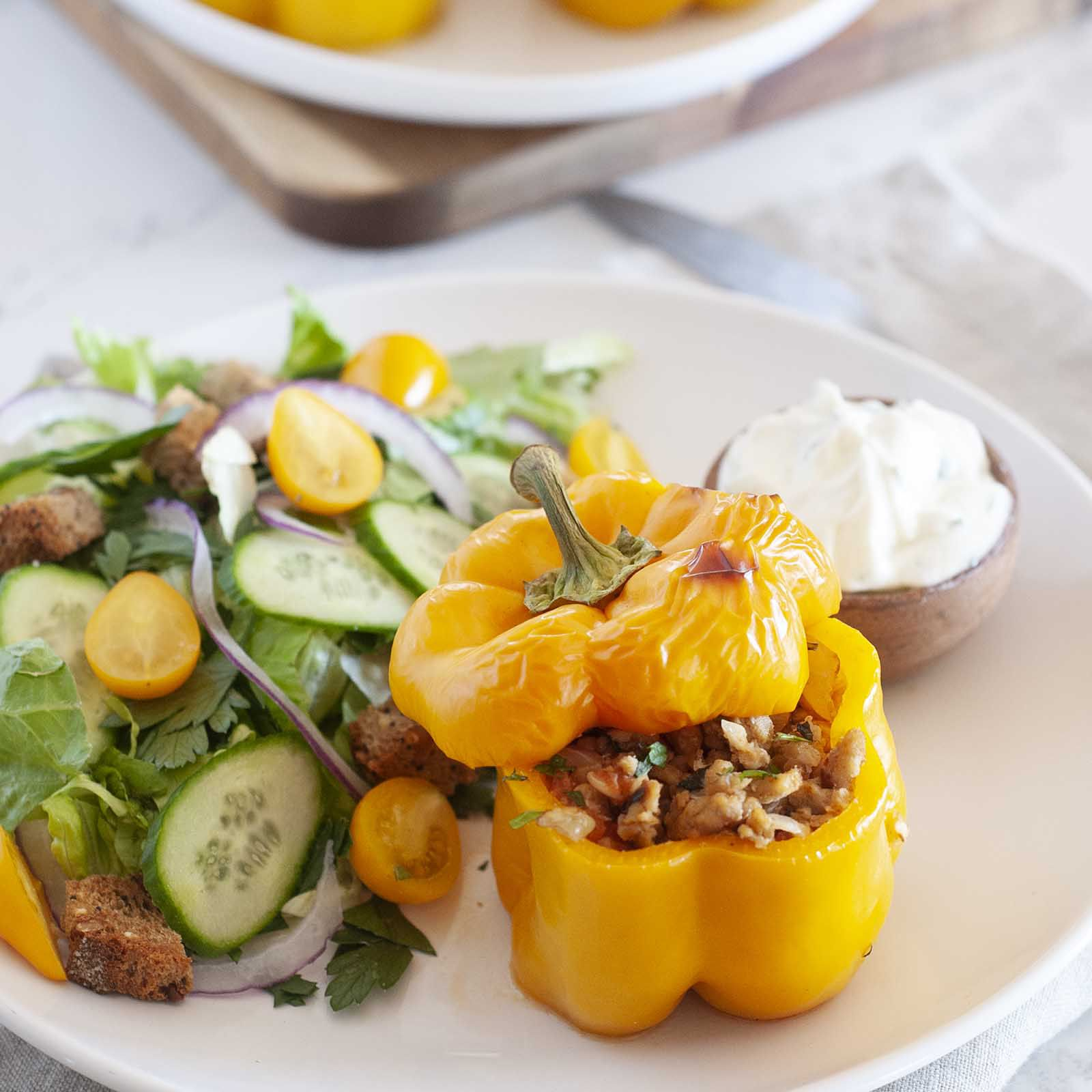 Healthy stuffed pepper with chicken is on a plate with the top askew to reveal the ground chicken filling. A yogurt sauce and garden salad are on the plate as well. Additional peppers are behind the plate.