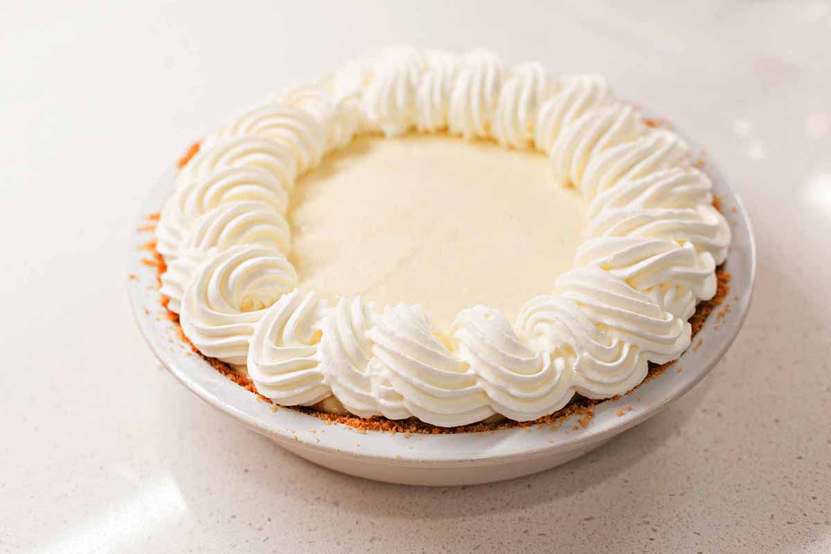 Whole banana cream pie with whipped cream swirls on top set against a white background.