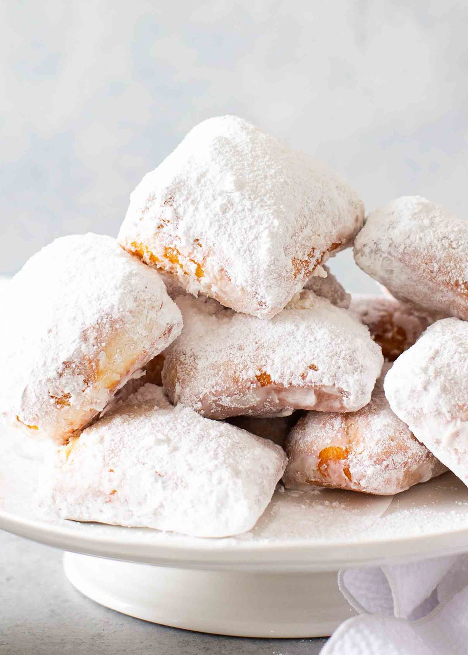 New Orleans Beignets stacked on a cake plate with two cups of espresso visible to the left and a paper towel to the right.