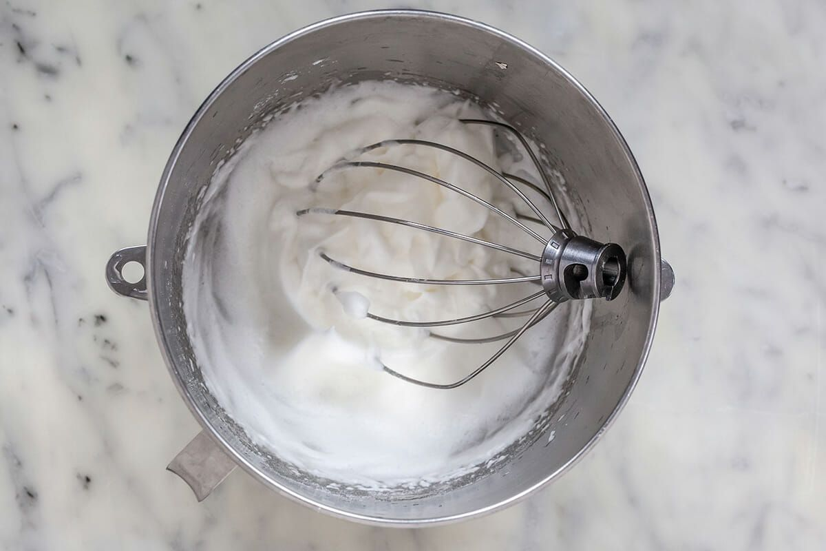 Whipped cream in a metal bowl to make avchocolate mousse recipe.