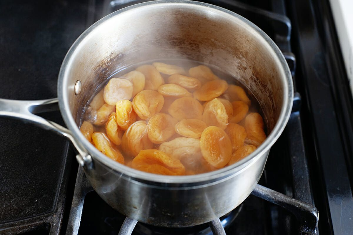 A pot sits on a gas stove and has dried apricots and liquid inside.