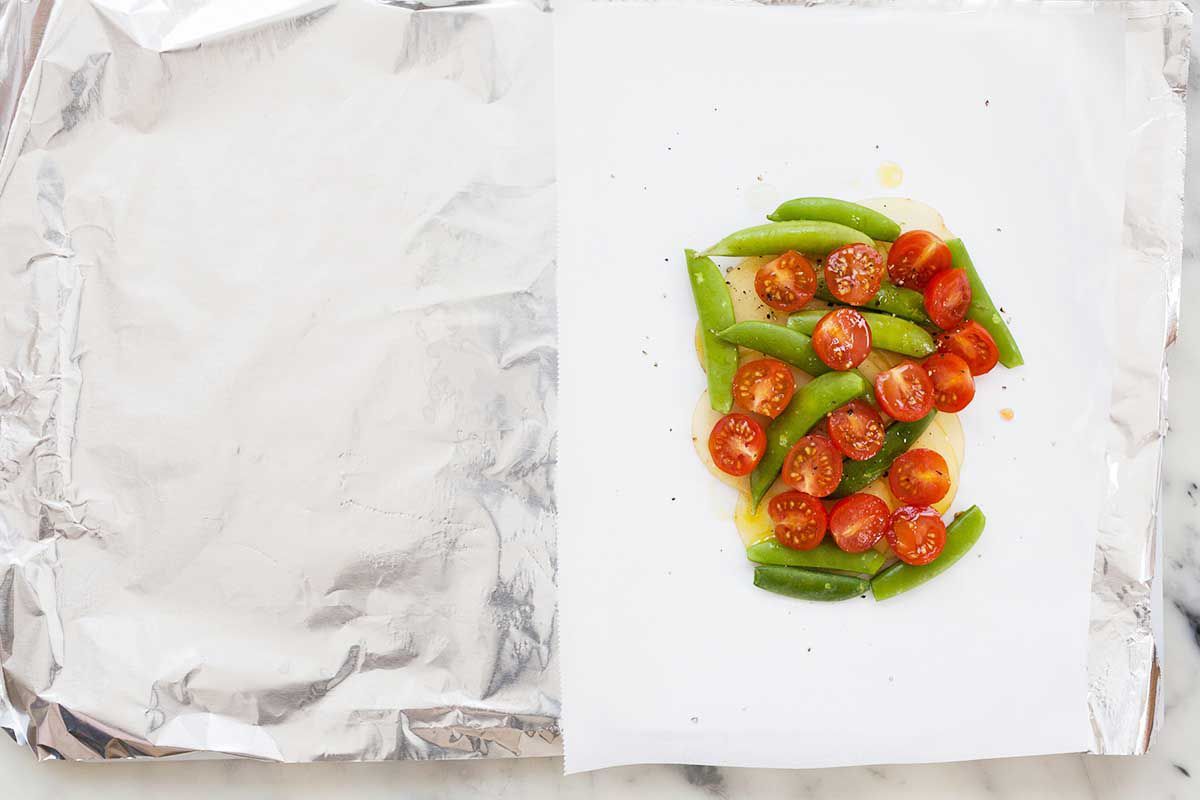 Olive oil coated cherry tomatoe halves and sugar snap peas rest on a piece of parchment paper. The paper covers half of a large sheet of foil.