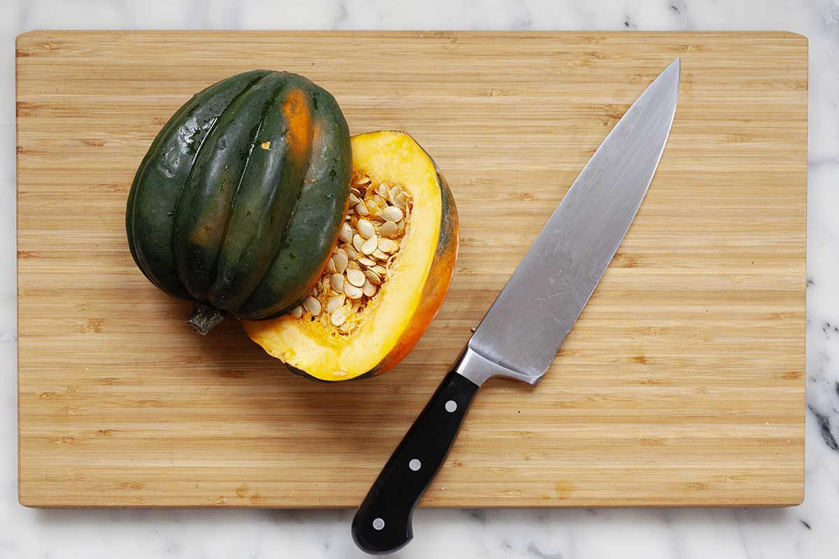 Acorn Sqush sliced in half on woodin cutting board with a long knife nearby.