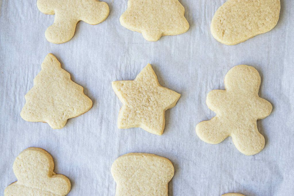 Christmas cookies cut into shapes and set on a parchment lined baking sheet.