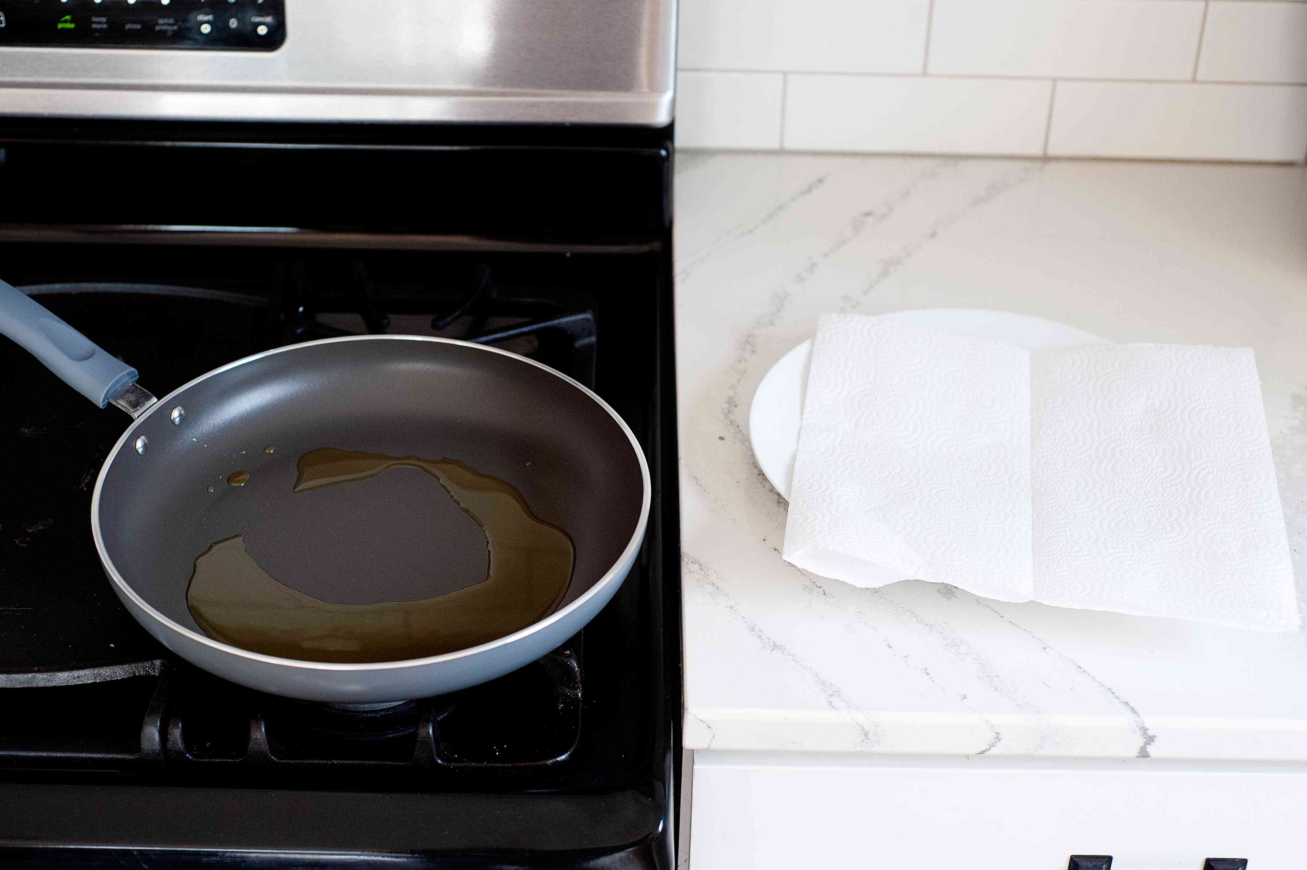 Frying pan with oil and a plate covered with a paper towel to make Kicha (Eritrean Flatbread).