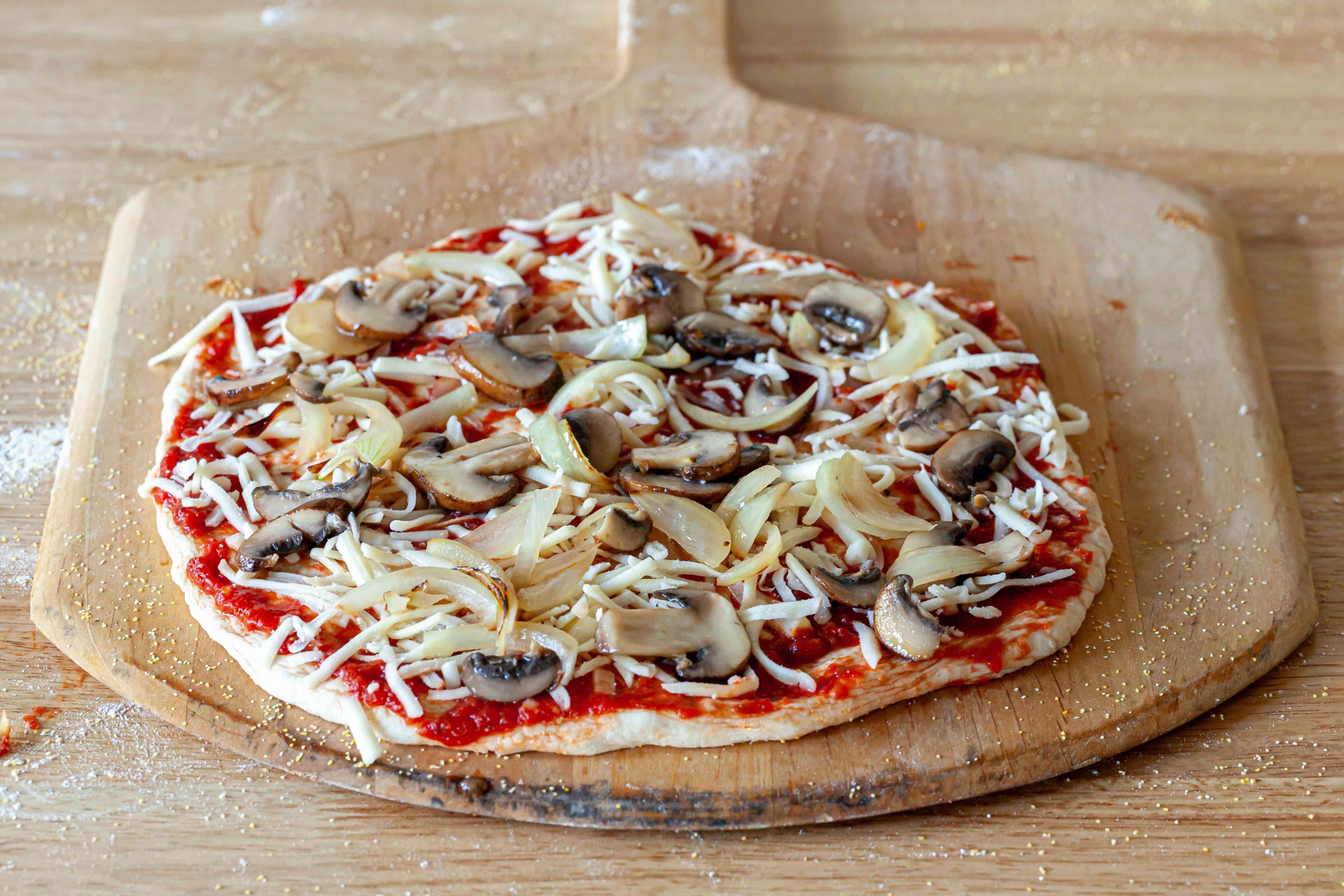 Pizza ingredients spread on pizza dough.