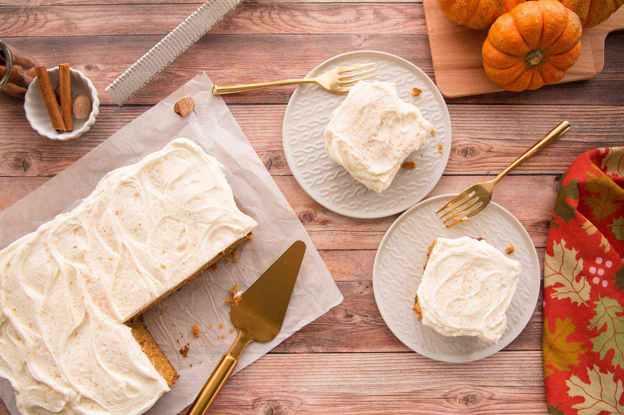 Pumpkin Snack Cake frosted with cream cheese is set on a table with two plates with pieces of cake to the right.