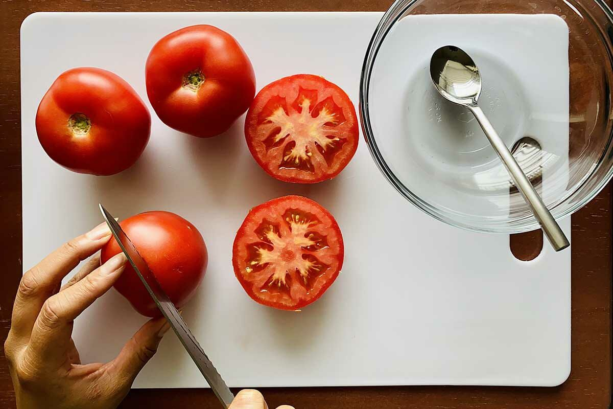 Tomatoes being halved on a cutting board with a glass bowl and spoon set to the right.