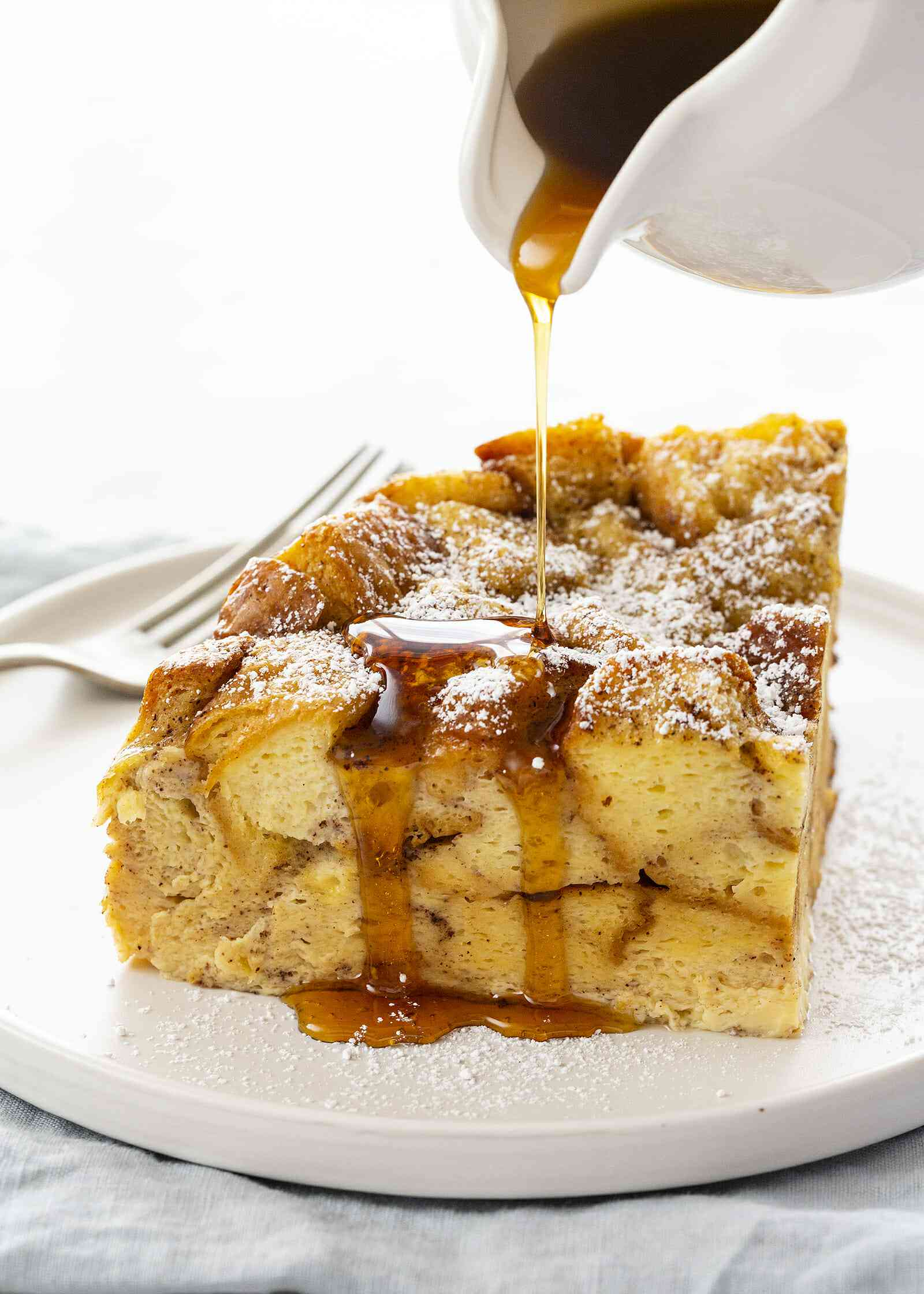 Crockpot French Toast Casserole - slice french toast casserole on plate with syrup and fork