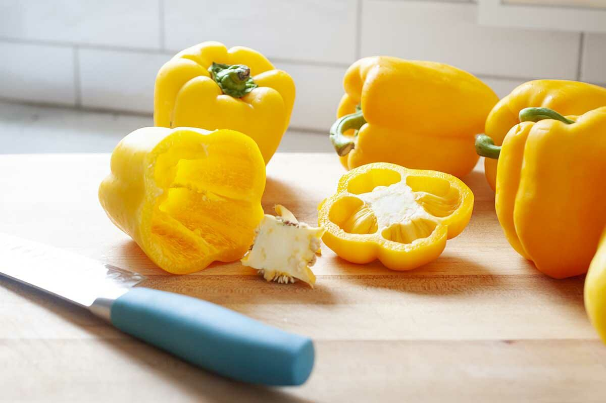Side view of yellow bell peppers on a cutting board with a chef's knife to the left.