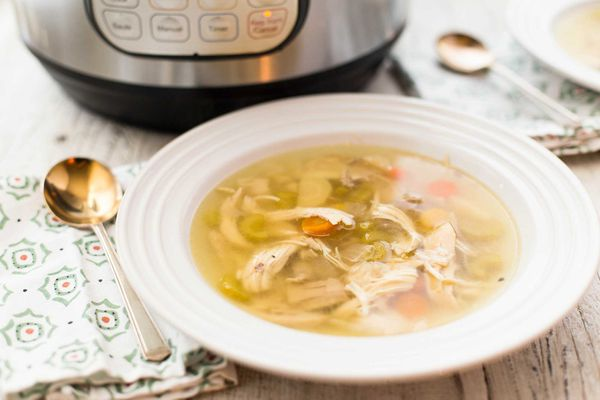 Instant pot chicken noodle soup in a bowl with the instant pot in partial view behind it.