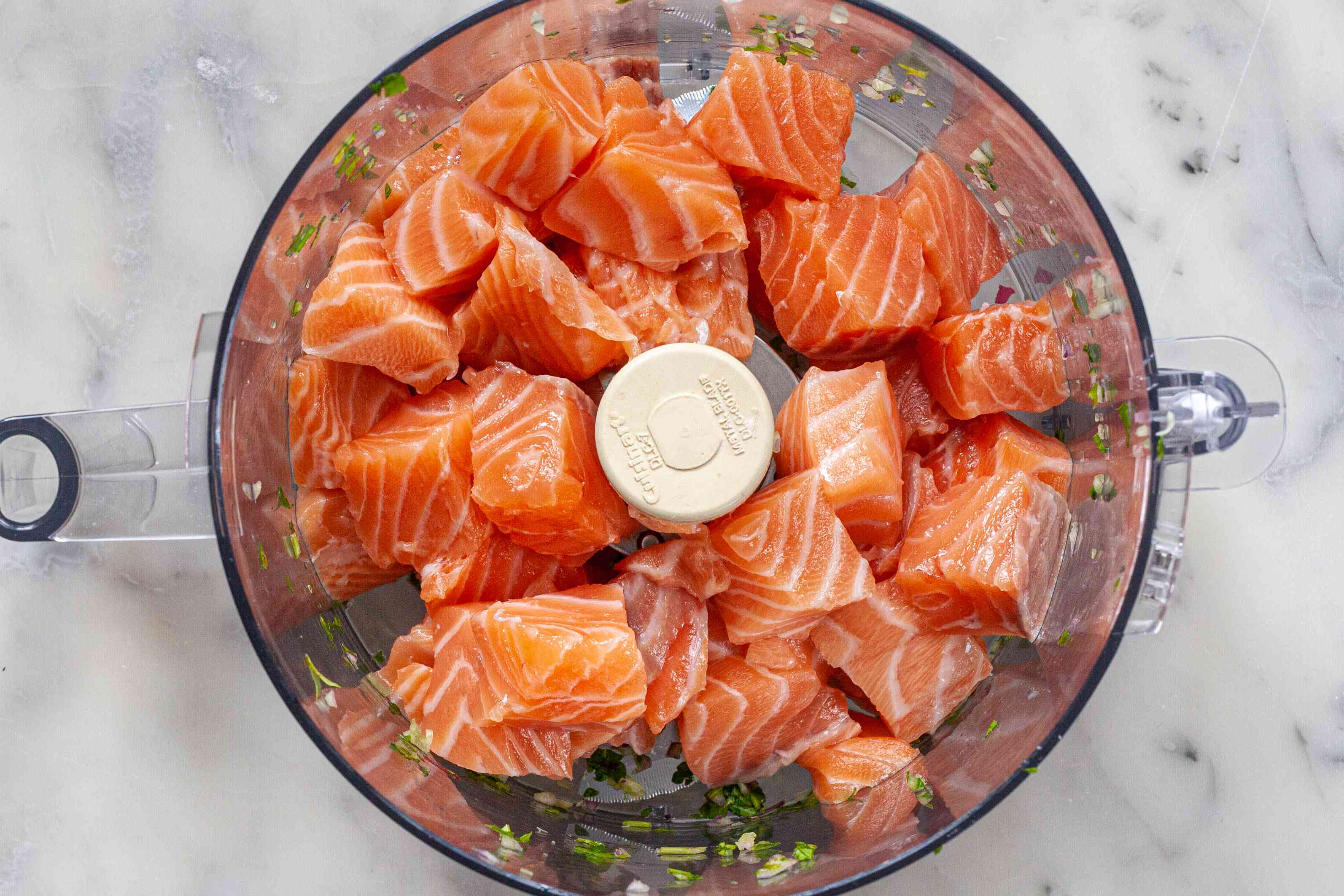 Cubed raw salmon in a food processor to make salmon burgers.