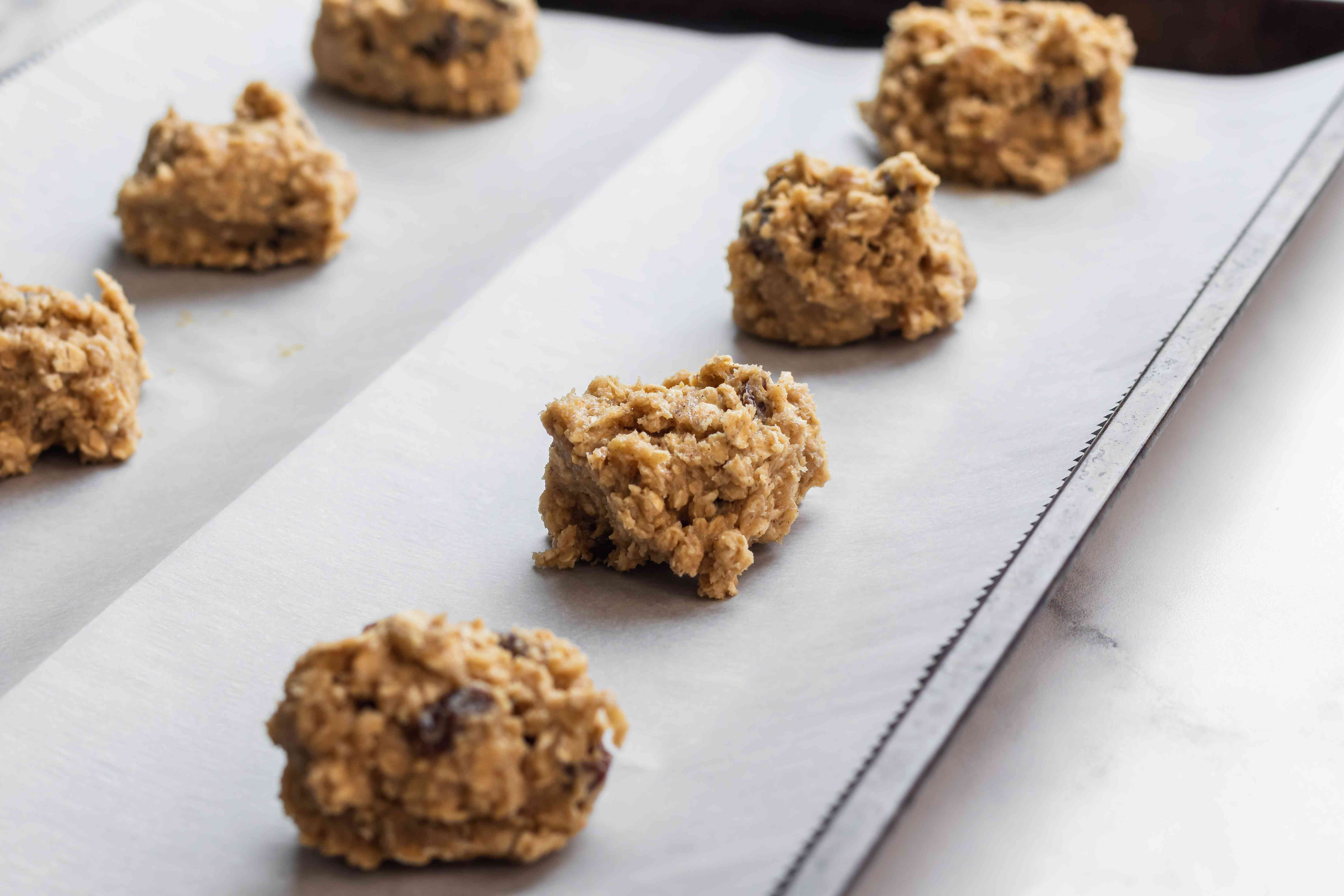 Oatmeal Raisin Cookies scooped on a parchment lined baking sheet.