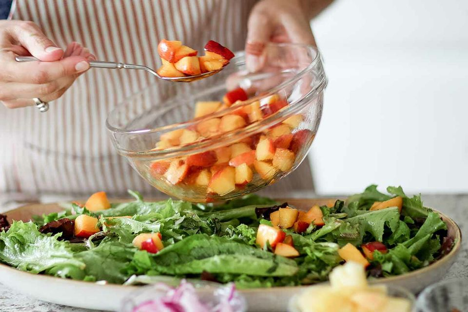 Salad recipe with peaches, goat cheese, and pistachios plate the salads