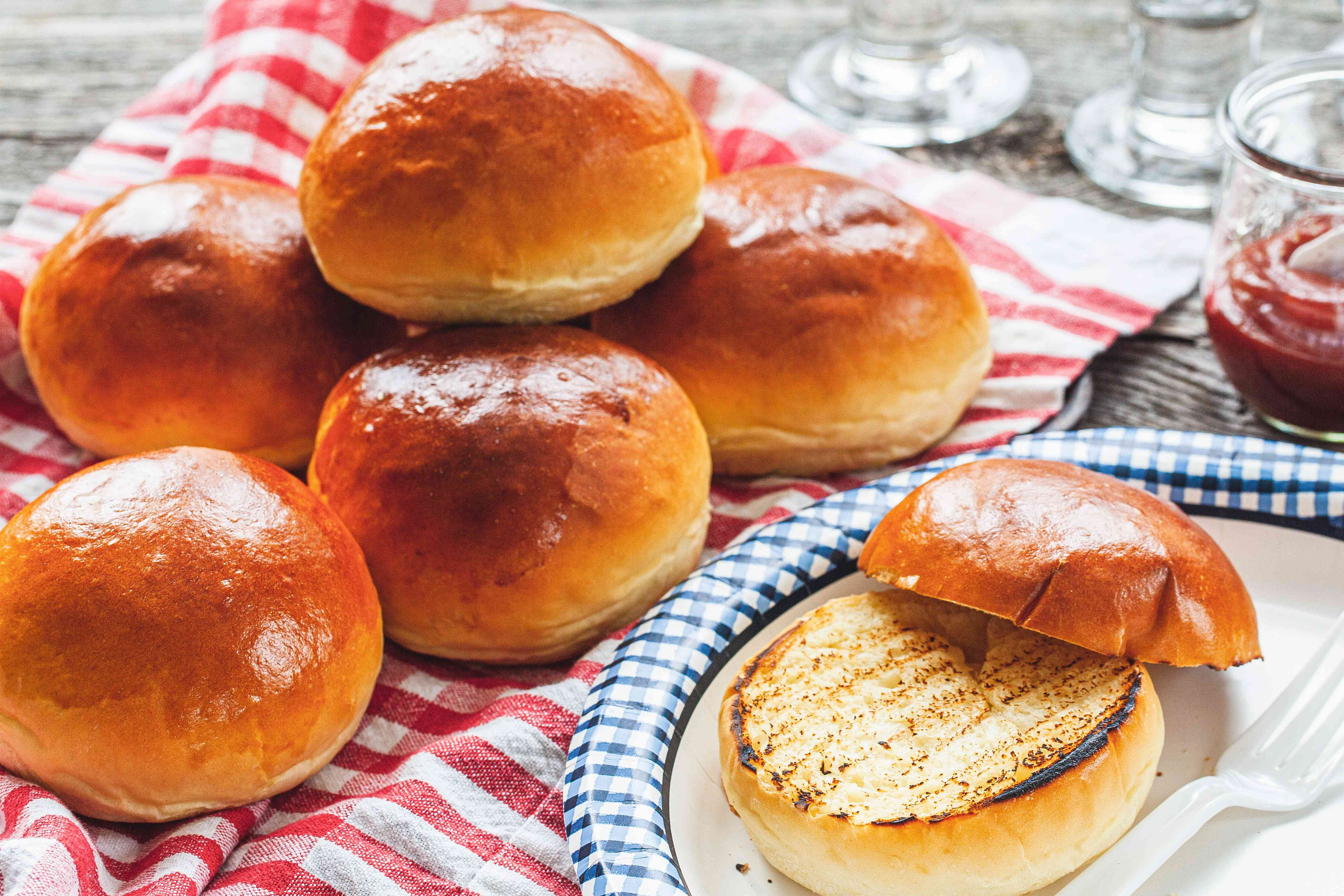 Homemade hamburger buns grilled and on a checkered linen.