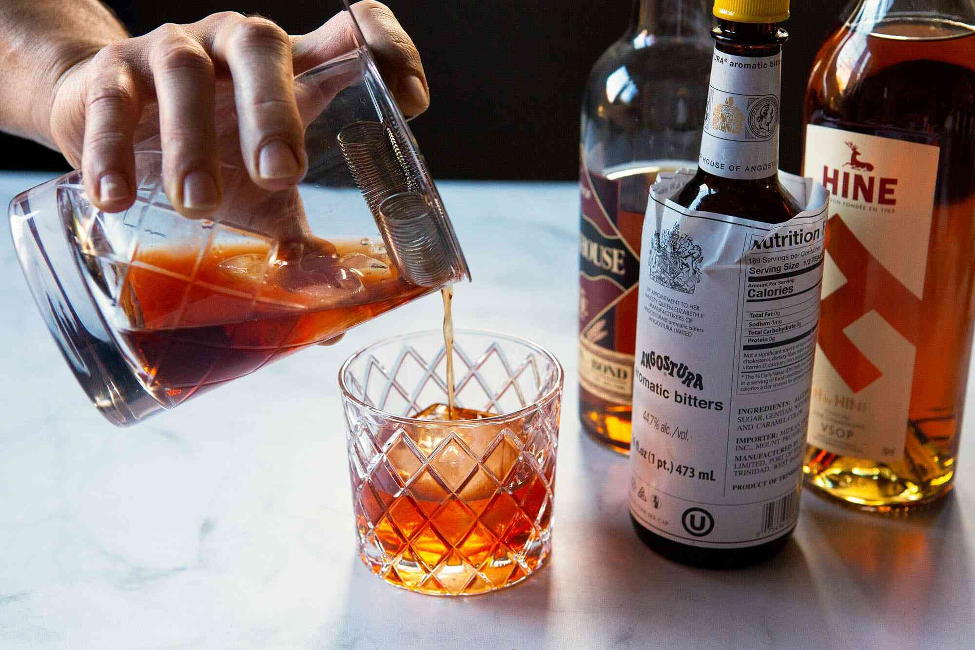 A Vieux carre is being strained into a whiskey glass. Bottles for the cocktail are to the right.