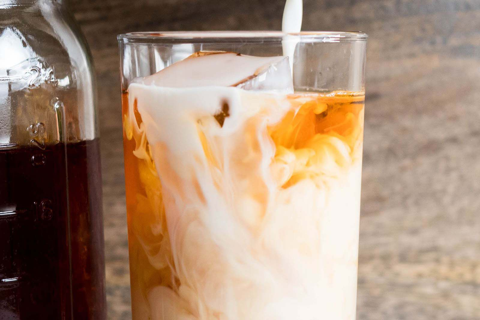 Milk being poured into a glass of iced chai